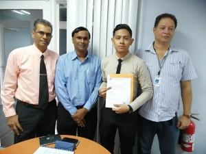 De afgestudeerde student Economie, Gianni Smith BSc, met leden van de examencommissie Adekus: Ramdath Dwarka, Bisoenpersad Mathoera en Michiel Bilkerdijk